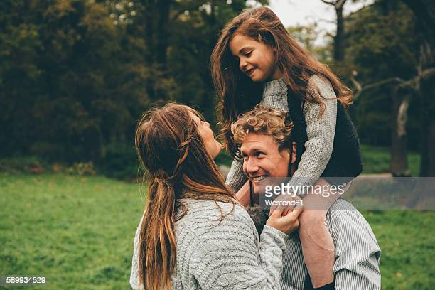 Happy young couple with little girl on her father's shoulders at autumnal park