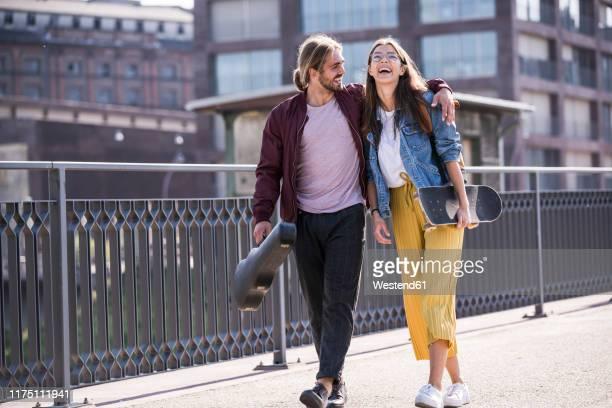 happy young couple with skateboard walking on a bridge - mannheim stock-fotos und bilder