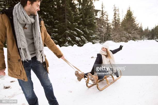 happy young couple with sledge in winter forest - ziehen stock-fotos und bilder