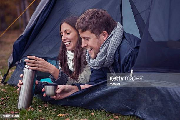 Happy young couple with thermos lying in tent at forest