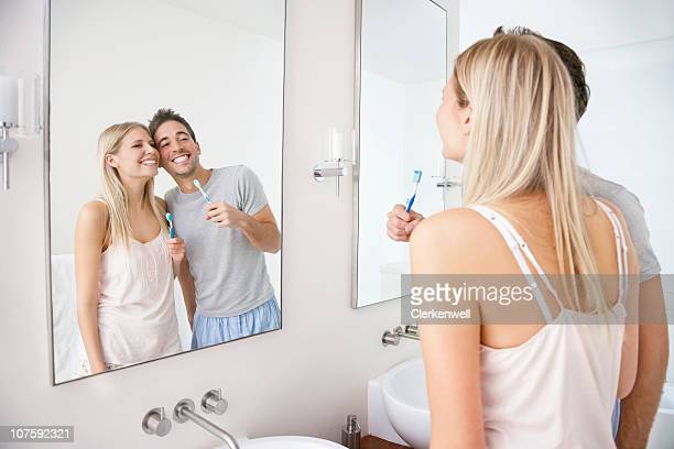 happy young couple with tooth brushes in front of bathroom mirror - vanity mirror stock photos and pictures