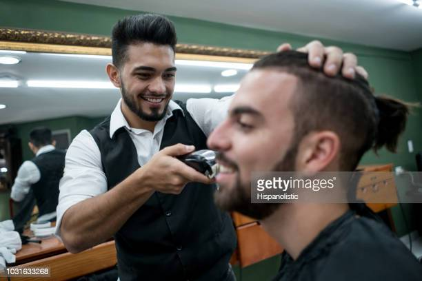 happy young customer getting his regular beard trim at the barber shop - hispanolistic stock photos and pictures