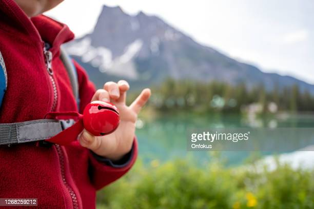 happy young cute redhead boy walking on trail wearing bear bell in summer - bear tracks stock pictures, royalty-free photos & images