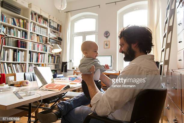 Happy young designer with baby son in home office