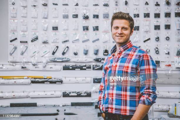happy young entrepreneur man standing in his store - information equipment stock pictures, royalty-free photos & images
