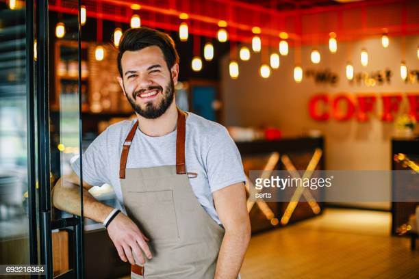 happy young entrepreneur man standing in the doorway of his store - happy merchant stock pictures, royalty-free photos & images