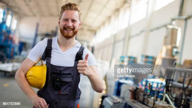 gelukkig jonge fabrieksarbeider met gele helm - technicus stockfoto's en -beelden