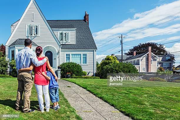 Heureux jeune famille en admirant la maison