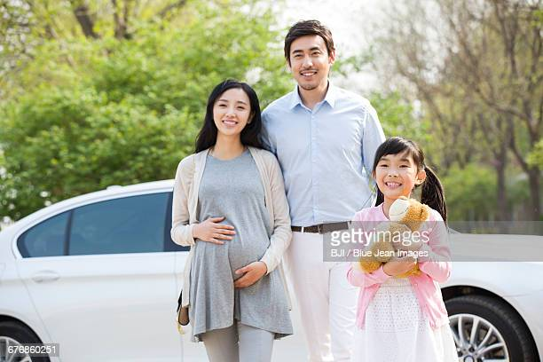 Happy young family and car
