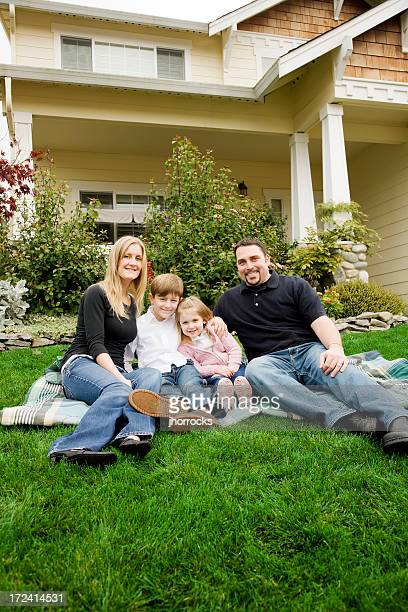 Glückliche junge Familie zu Hause im Vorgarten