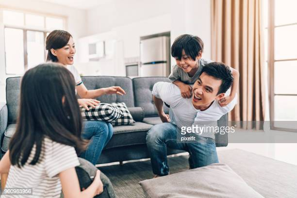 happy young family at home - carrying a person on shoulders stock photos and pictures