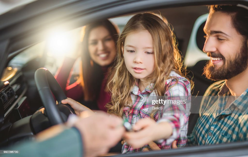 Happy young family buying their new car. : Stock Photo