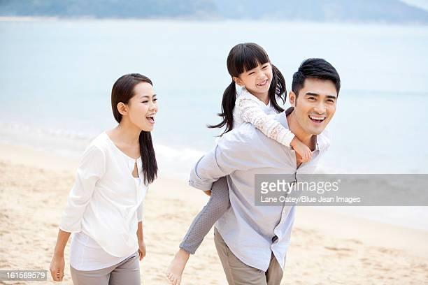 Happy young family enjoying the beautiful beach of Repulse Bay, Hong Kong