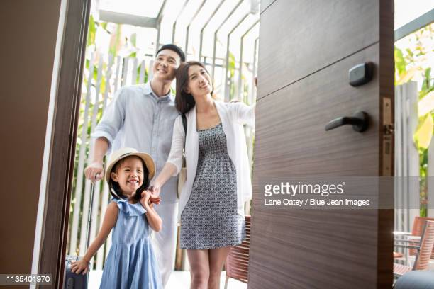 happy young family entering hotel room - 到着 ストックフォトと画像