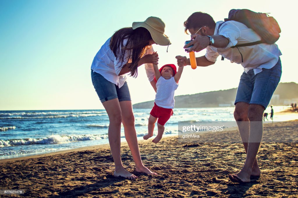 Happy young family having fun running on beach at sunset : Stock Photo