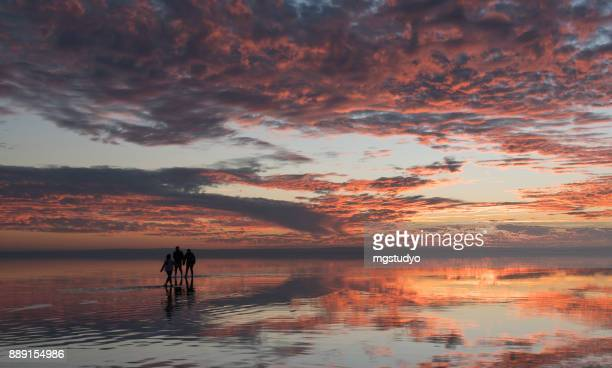 happy young family having fun running on salt lake at sunset - beautiful turkish girl stock pictures, royalty-free photos & images