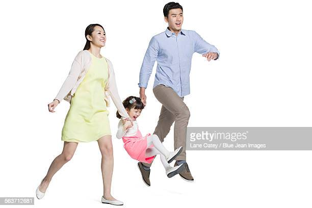 Happy young family holding hands running