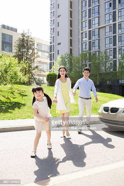 Happy young family holding hands walking