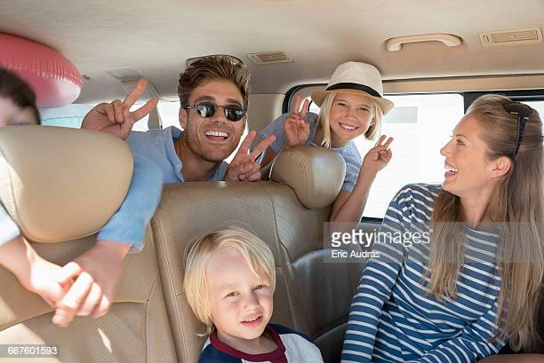happy young family in car for vacation - family inside car stock photos and pictures