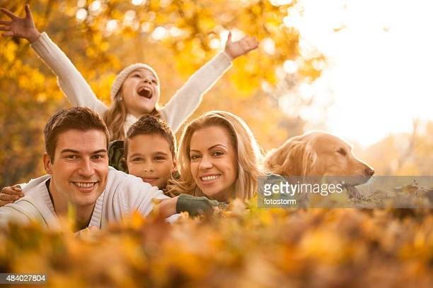 Happy young family in the autumn park with dog