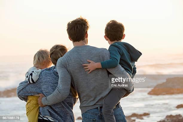 happy young family looking at sea on the beach at sunset - aussicht genießen stock-fotos und bilder