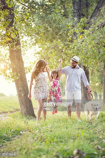 Familia joven feliz en un día de verano con su perro