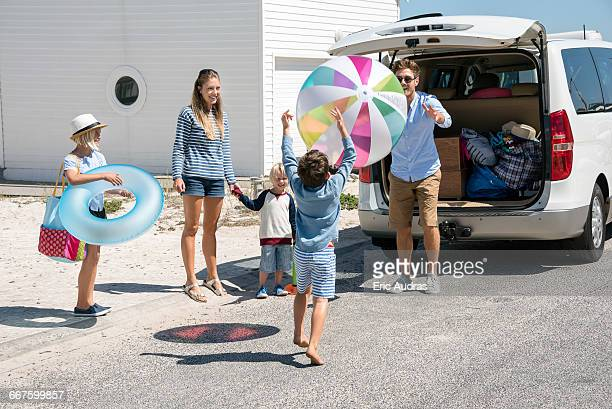 Happy young family packing car with beach gears for vacation