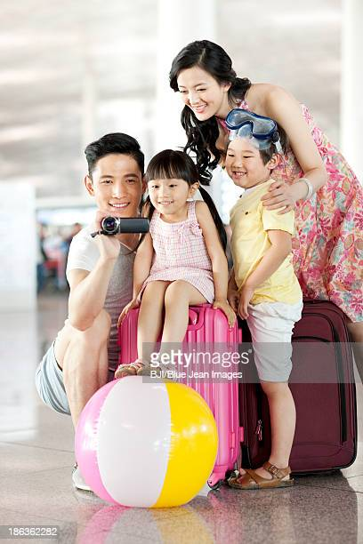 Happy young family photographing at the airport