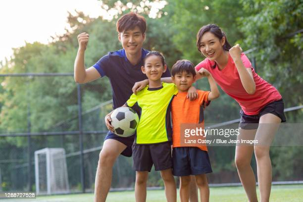 happy young family playing football on soccer field - 運動隊制服 個照片及圖片檔
