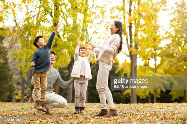 happy young family playing with bubbles in autumn woods - homem pegando mulher imagens e fotografias de stock