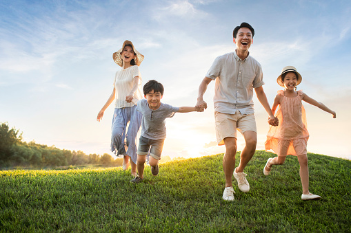 Happy young family running on meadow - gettyimageskorea