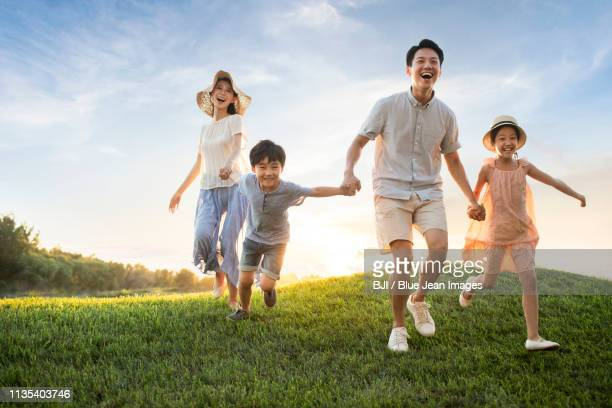 happy young family running on meadow - asien stock-fotos und bilder