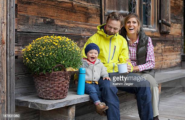 happy young family sitting on bench, drinking tea