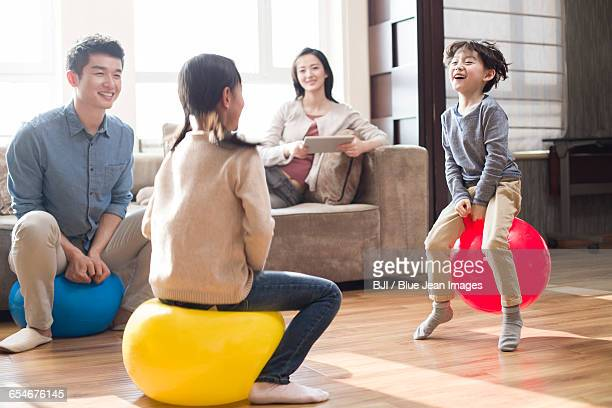 Happy young family sitting on hoppity horses at home