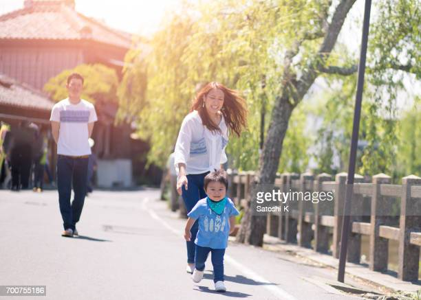 Happy young family strolling along river