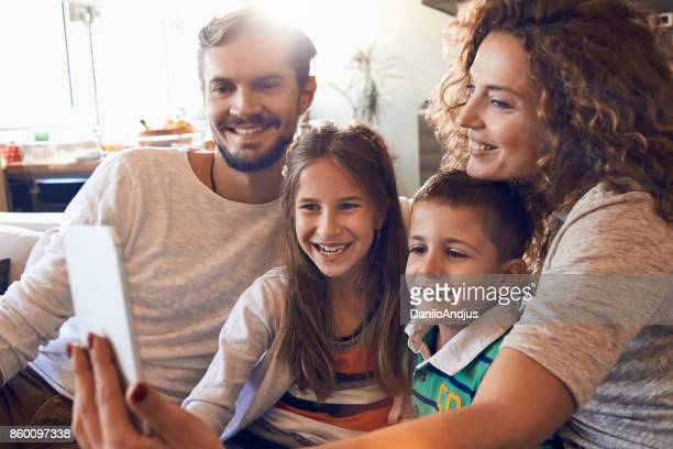 happy young family taking a selfie at home