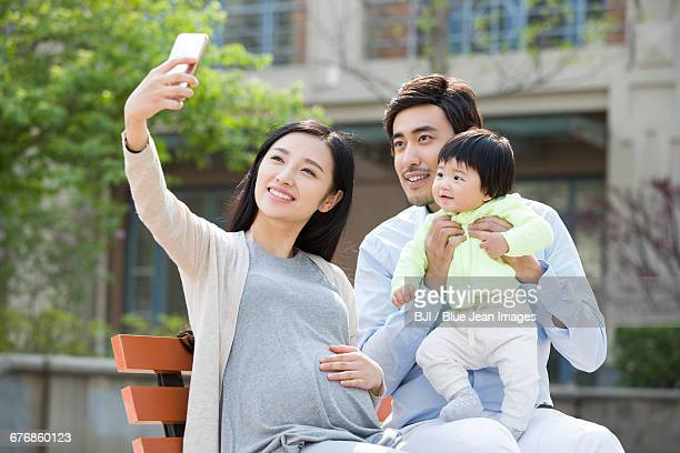 Happy young family taking self portrait with a smart phone