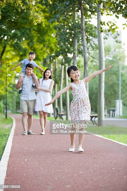 Happy young family walking in park