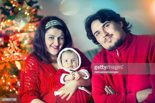 Happy Young Family with Baby by the Christmas Tree