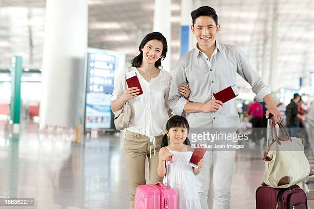 Happy young family with flight tickets and passports at the airport