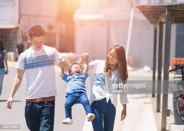 幸せな若い父と母、子を持ち上げる