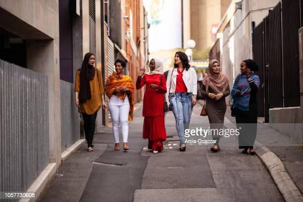 happy young female friends wearing hijab and walking in laneway in city - religión fotografías e imágenes de stock
