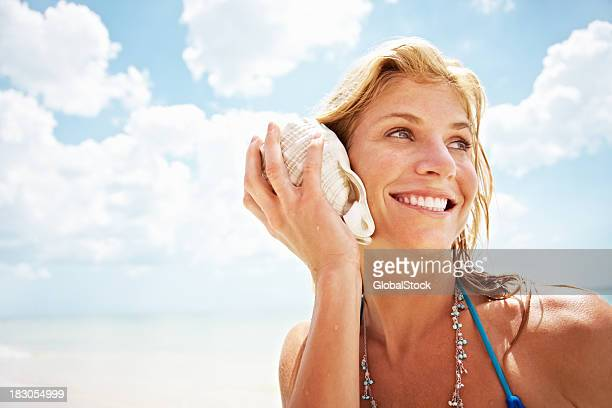 happy young female holding a conch shell against sky - conch shell stock pictures, royalty-free photos & images