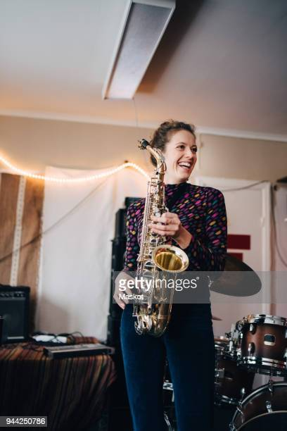 Happy young female musician playing saxophone in rehearsal studio
