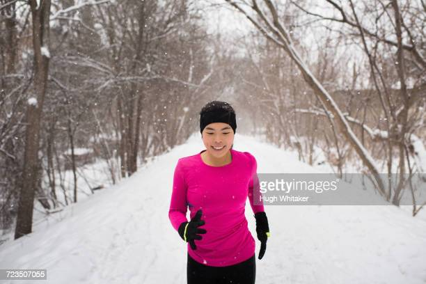 happy young female runner in knit hat running in snow covered tree lined park - peterborough ontario stock photos and pictures