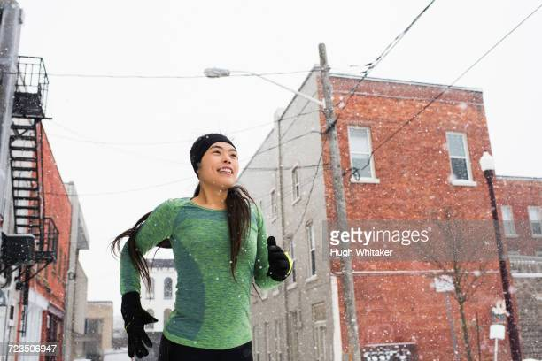 happy young female runner in knit hat running in snowy street - peterborough ontario stock photos and pictures