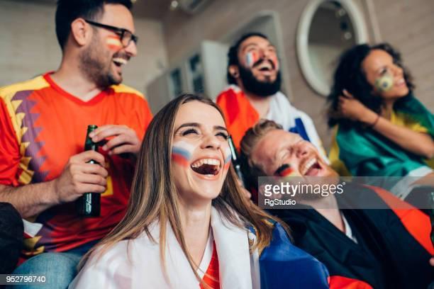 Glückliche junge weibliche Unterstützer der russischen Fußball-Nationalmannschaft Spiel mit Freunden zu schauen