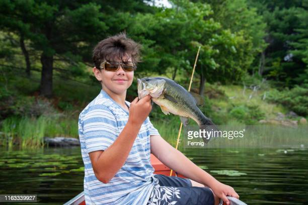 happy young fisherman in a canoe with his catch - largemouth bass stock pictures, royalty-free photos & images