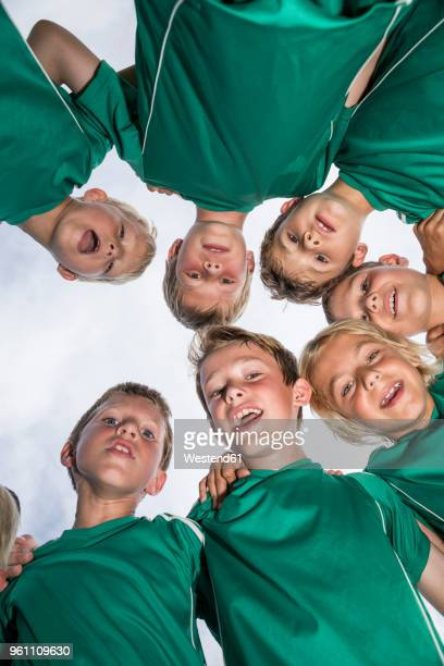 happy young football players huddling - équipe de football photos et images de collection