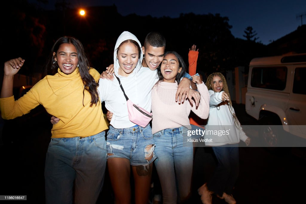 Happy young friends dancing at night : Stock-Foto